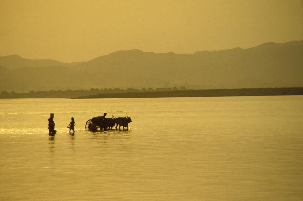 BURMA, PAGAN, WATERBEARERS AND OX CART SILHOUTTED IN THE IRRAWADDY RIVER AT SUNSET