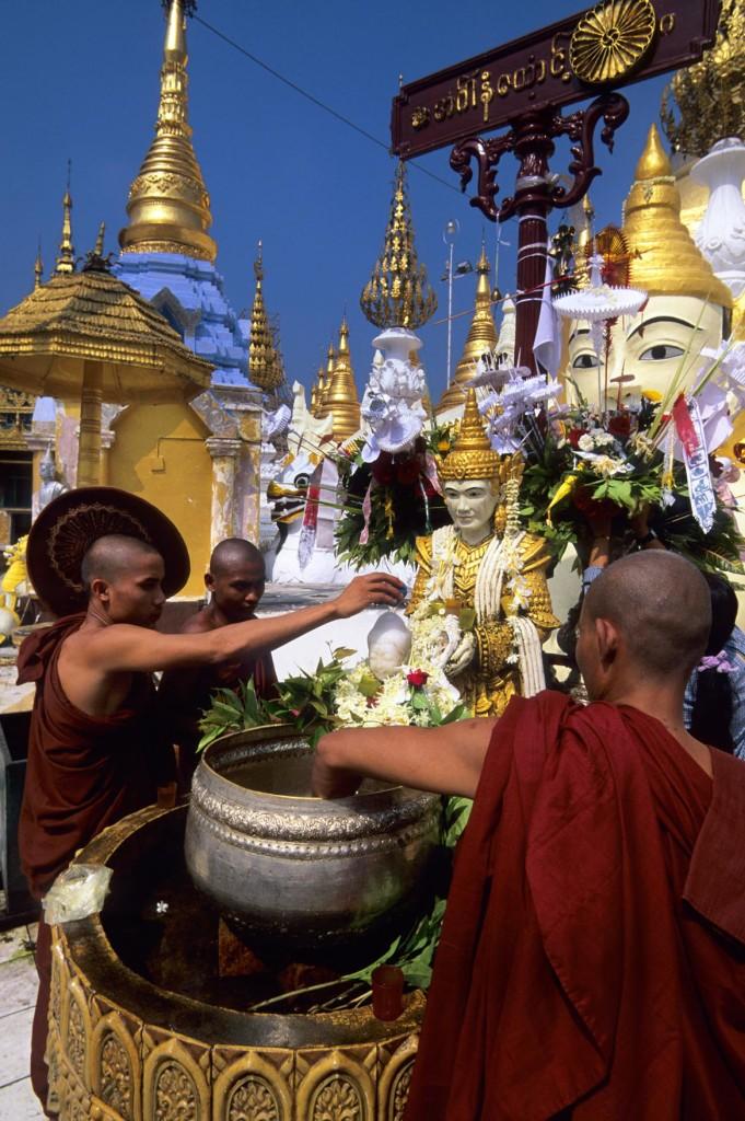 MYANMAR(BURMA), RANGOON, SHWEDAGON PAGODA, MONKS WORSHIPING, POURING WATER OVER BUDDHA STATUE